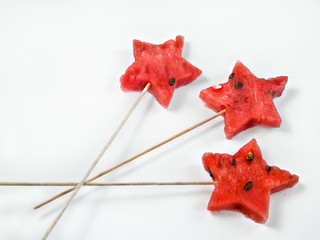 Asteriskes of ripe juicy fresh watermelon on long wooden skewers lie on a white background