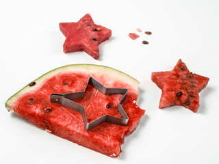The process of cutting figurines from a piece of ripe juicy fresh watermelon on a white background