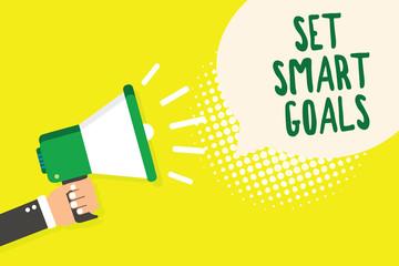 Word writing text Set Smart Goals. Business concept for Establish achievable objectives Make good business plans Man holding megaphone loudspeaker speech bubble yellow background halftone.