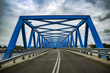 Blue metal bridge with clouds in the background.