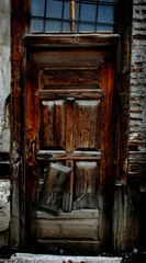 Broken old door on old cracked wall