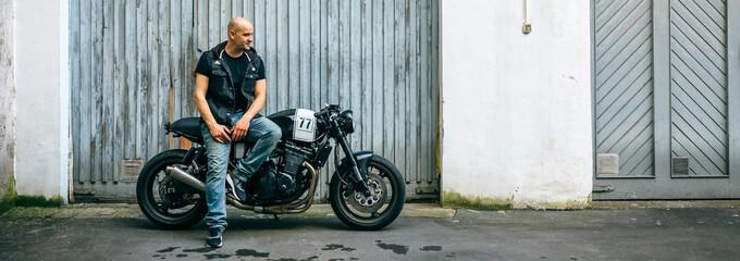 Biker posing with a custom motorcycle in front of the garage door