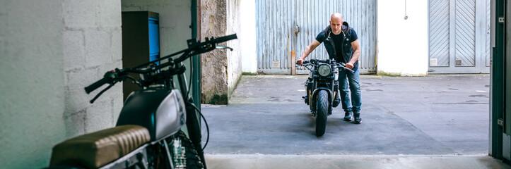 Front view of biker taking custom motorbike to the garage