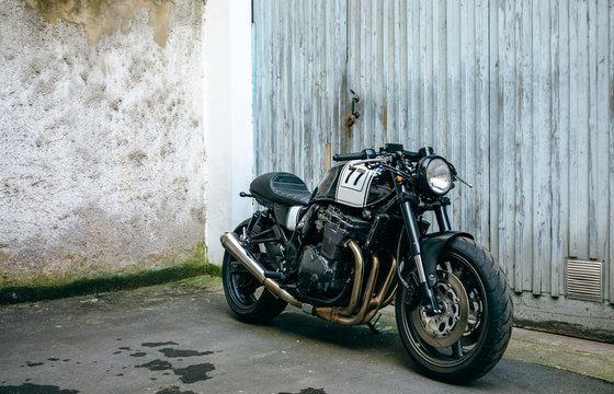 Shiny customized motorcycle parked in front of garage door
