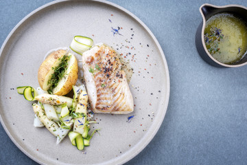 Modern style German fried cod fish filet with white asparagus tips and roast potatoes as top view on a plate with copy space right