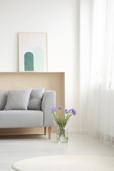 Blue flowers next to grey couch with cushions in simple living room interior with poster. Real photo