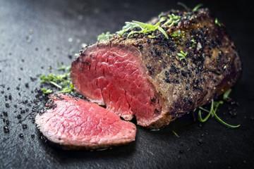 Traditionelles Barbecue dry aged Wagyu Rinderfilet Steak mit Kräuter als closeup auf einem schwarzen Board