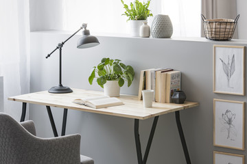 Real photo of wooden desk with fresh plant, black lamp, coffee cup and books standing on half-wall with simple posters Wall mural