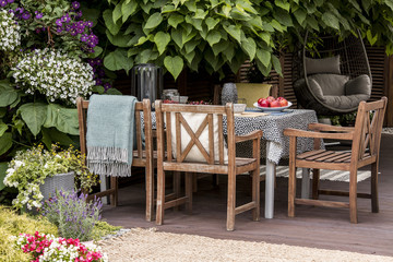 Real photo of garden furniture on beautiful terrace full of flowers and plants