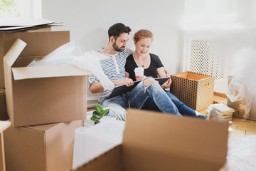Lovely couple looking at photo album while unpacking stuff after relocation to new home