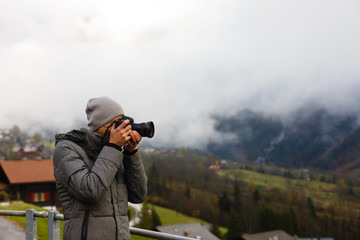 Nature photographer tourist with camera shoots while standing of the mountain.