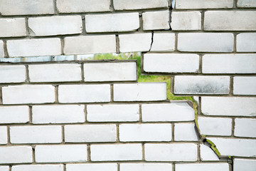 crack in the fence of gray bricks on a summer day