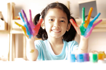 The little girl is showing color painted on hands