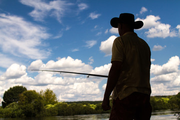 Fishing on the lake. Fisheries. Fisherman on the lake shore on a cloudy sky background