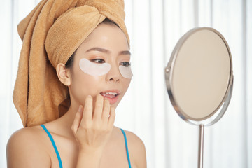 Attractive Asian female with under-eye pads looking in mirror and applying lipstick while performing skincare routine