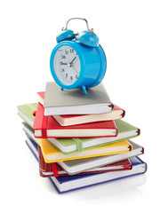 notebooks and alarm clock at white background