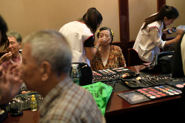 Participants get make-up applied before a photo shoot event organized to recreate wedding photos for elderly couples, who have been married for more than 50 years, a day ahead of the Qixi festival in Tianjin