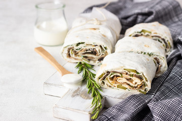Rolls with mushroom, cukes and cream cheese served with cream and rosemary on white wooden cutting board. Thin Armenian pita bread or lavash. Snack.