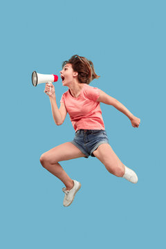 Beautiful young woman jumping with megaphone isolated over blue background. Runnin girl in motion or movement. Human emotions and facial expressions concept