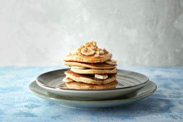 Plate with tasty pancakes, walnuts and sliced banana on table