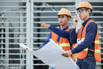 Side view of two Asian men with blueprint looking at distance and talking on walkie-talkie while standing on construction site