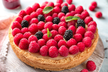 Delicious cheesecake with raspberries on table