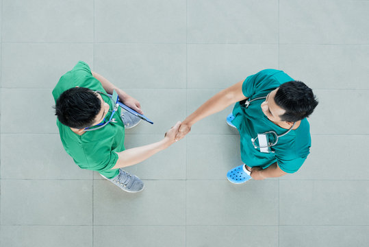 From above shot of two men in scrubs shaking hands while standing on tiled floor of hospital floor