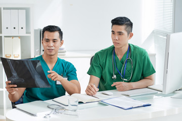 Two Asian men in scrubs looking at bone X-ray picture while sitting at desk in hospital office