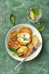 Plate with zucchini pancakes and glass of water on table