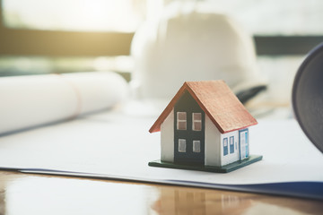 House model on table in office with blueprints,engineer inspection in workplace for architectural plan,sketching a construction project ,selective focus,Business construction concept.
