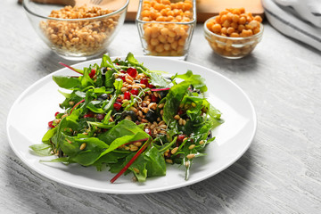 Plate with healthy fresh salad on white wooden table