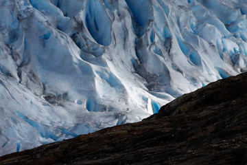 Light creating strong diagonals with shade on the surface of a glacier