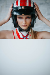 Beautiful sexy woman with stylish makeup in biker helmet. Copy space for advertising biker products. Extreme lifestyle concept.