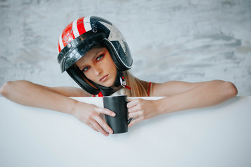 Female biker girl with black full face motorcycle helmet. Copy space for advertising biker products. Extreme lifestyle concept.