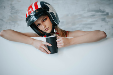 Female biker girl with black full face motorcycle helmet.Copy space for advertising biker products. Extreme lifestyle concept. Sexy girls in formula one style