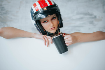 Female biker girl with black full face motorcycle helmet.Copy space for advertising biker products. Extreme lifestyle concept.Sexy girls in formula one style