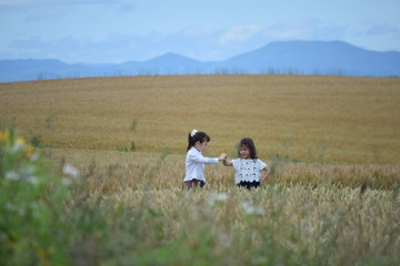 Two girls playing in the wheat field