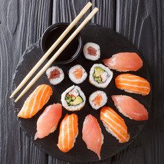 Japanese menu. Tasty set of sushi with salmon and tuna, California rolls, maki, soy sauce closeup. Top view
