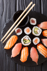 Served a set of sushi with salmon and tuna, California rolls, maki, soy sauce closeup on the table. Vertical top view