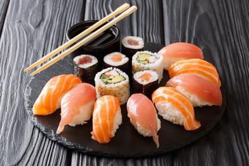 Japanese sushi on a rustic dark background. Sushi rolls, nigiri, maki, soy sauce. Sushi set on a table. background. Asian food. Horizontal