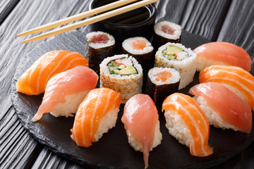 Sushi rolls set served on black stone slate on dark background