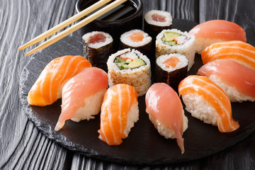 set of sushi and rolls with salmon and tuna, avocado, california, maki, soy sauce, chopsticks close-up. horizontal