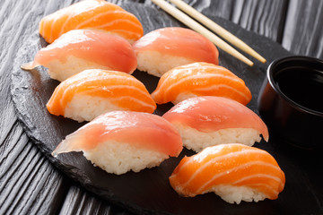 Tasty dietary sushi with salmon and tuna, soy sauce close-up on a black slate. horizontal