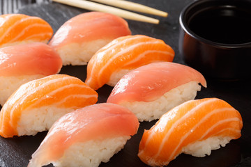 Japanese food: a set of sushi with salmon and tuna, soy sauce close-up on a black board. horizontal