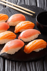 Sushi set with salmon and tuna, soy sauce close-up on a black slate. vertical