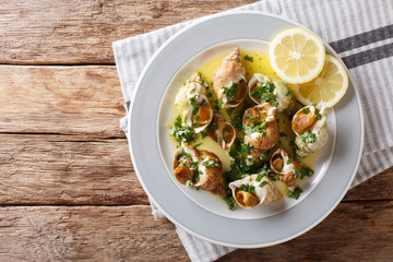 Foto op Plexiglas Schaaldieren French cuisine: sea snails bulot with garlic sauce and lemon close-up. horizontal top view from above