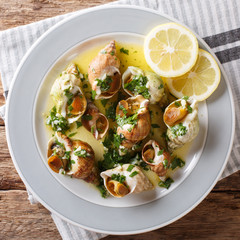 French recipe Whelks with a sauce of butter, garlic and parsley, lemon close-up. top view from above