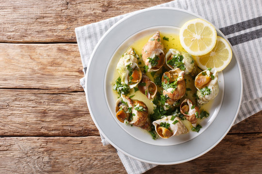 French cuisine: sea snails bulot with garlic sauce and lemon close-up. horizontal top view from above