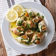 Bulots Cuits - Cooked Waved Whelks with a sauce of butter, garlic and parsley, lemon close-up. top view from above