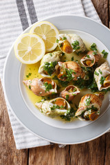 French shellfish bulot whelks served with a sauce of butter, garlic and parsley, lemon close-up. Vertical top view from above